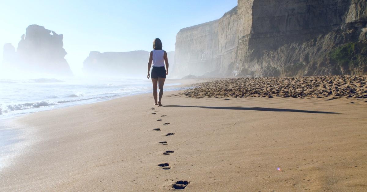 """Donna che cammina sulla spiaggia. """"Non importa se vai piano, l'importante è che non ti fermi"""" Confucio"""